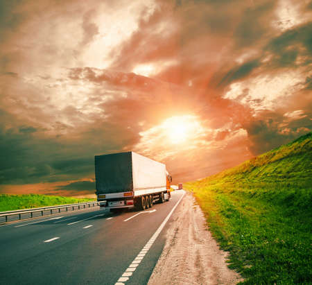 truck on highway: trucks under colorful sky