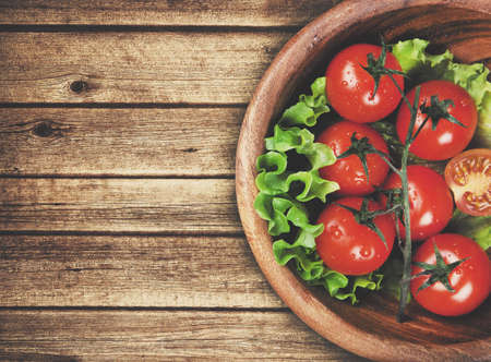 alimentacion sana: cuenco de madera con tomates cherry