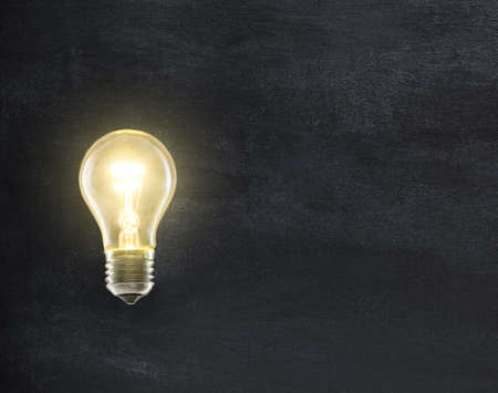 Light bulb lamp on blackboard background with copy space