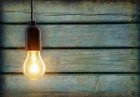 コピー スペースを持つ木製の背景の上に電球ランプ