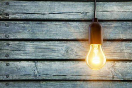 kilowatt: Light bulb lamp on wooden background with copy space