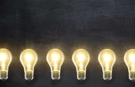 Light bulb lamps on blackboard background with copyspace