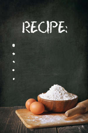 chalk board: Flour and eggs on a blackboard background. space for recipe