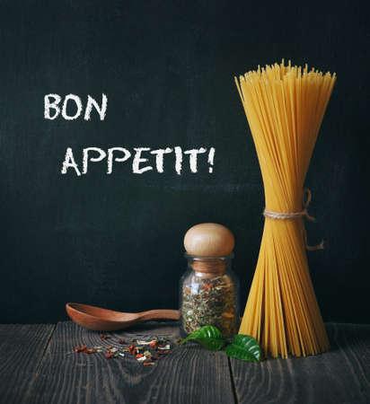 dinner menu: spaghetti and spices on blackboard background. bon appetit text Stock Photo