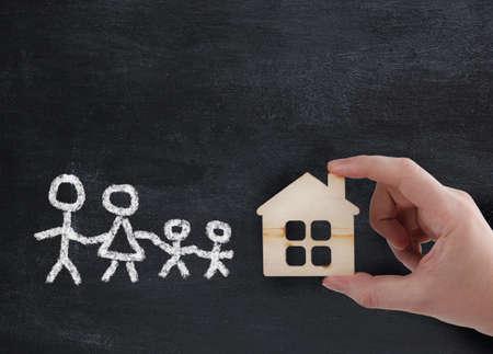 ruka drží nový dům pro rodinu - pojetí Reklamní fotografie