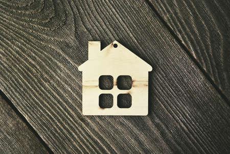 木製の背景にシンボルとしての家