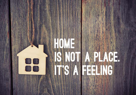 house as symbol on wooden background with quote