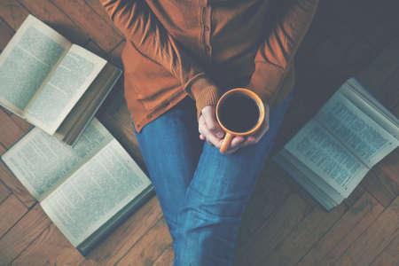 moudrost: dívka s přestávku s šálkem kávy po přečtení čerstvou knih nebo studují Reklamní fotografie