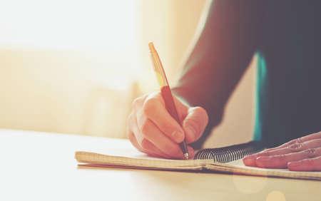 writing book: mani femminili con scrittura della penna sul taccuino