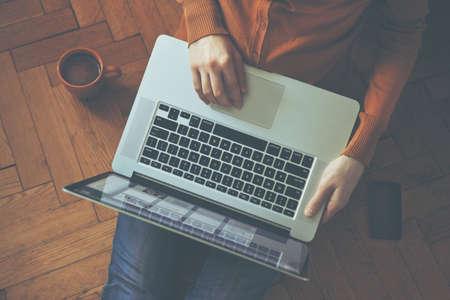 나무 바닥에 앉아 여자의 손에 노트북