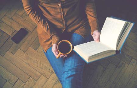 mujer leyendo libro: niña leyendo el libro y beber café fresco Foto de archivo
