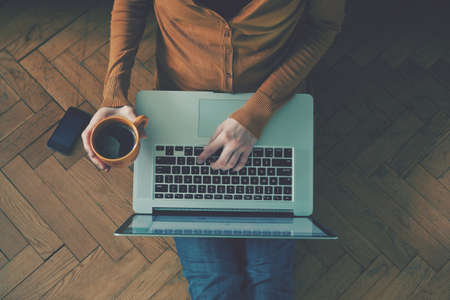 work from home: Laptop and coffee cup in girls hands sitting on a wooden floor