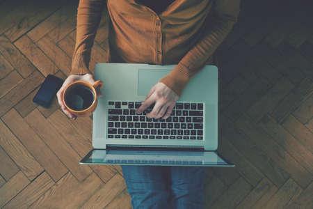 mujeres trabajando: Port�til y taza de caf� en las manos de las ni�as sentado en un suelo de madera
