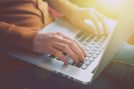 using a laptop: hands with laptop typing in sunlight Stock Photo