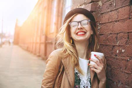 anteojos: Mujer alegre en el café de la calle consumición de la mañana la luz del sol Foto de archivo