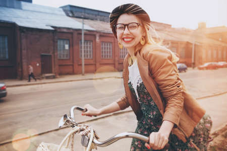 時尚女性騎自行車在早晨的陽光