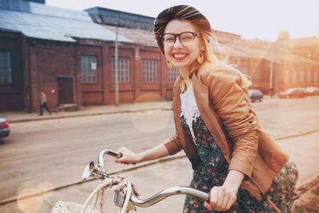 stylish woman riding on bike in morning sunshine