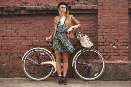 modieuze vrouw met vintage fiets op bakstenen muur achtergrond Stockfoto