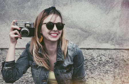 camera girl: happy girl with vintage camera taking photo on urban wall background Stock Photo