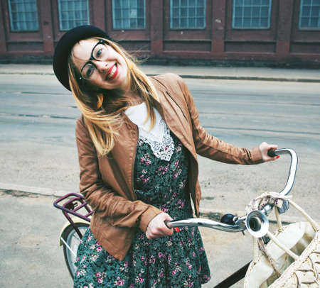 Cheerful  woman with a bike in a street