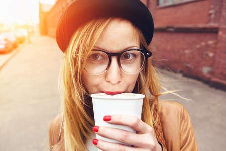 stylish woman in glasses drinking coffee in morning sunshine Standard-Bild