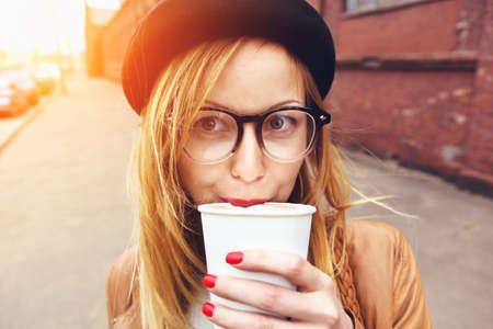 stylish woman in glasses drinking coffee in morning sunshine Imagens