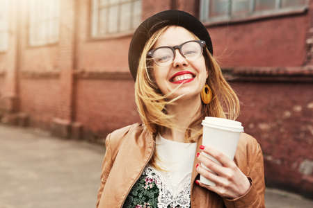 style woman: Cheerful woman in the street drinking morning coffee in sunshine light
