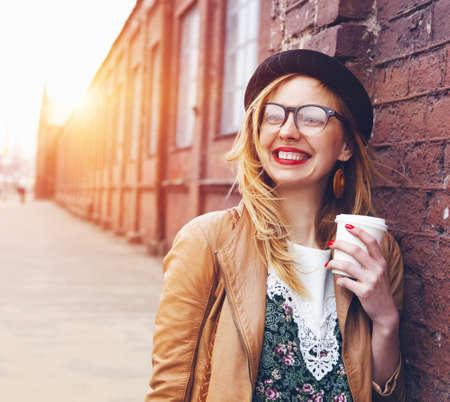 Vrolijke vrouw in de straat koffie drinken 's ochtends in de zon licht