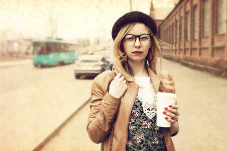 textured: Stylish woman in the street drinking morning coffee. Vintage paper textured Stock Photo
