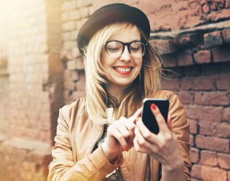 Stadsleven stijlvolle hipster meisje met behulp van een telefoon texting op smartphone app in een straat Stockfoto
