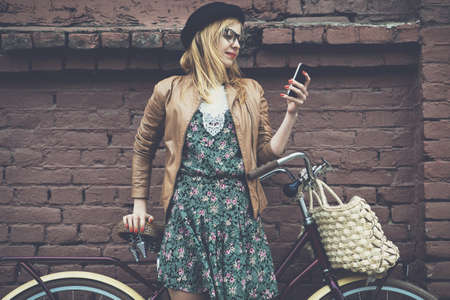 text: City lifestyle stylish hipster girl with bike using a phone texting on smartphone app in a street