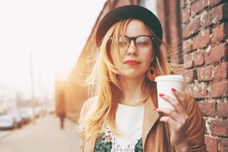 時尚的女人在大街上喝早上喝咖啡