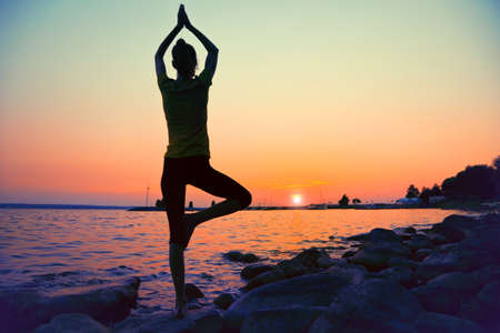 yoga girl: Silhouette woman practicing yoga posing on beach at sunset Stock Photo