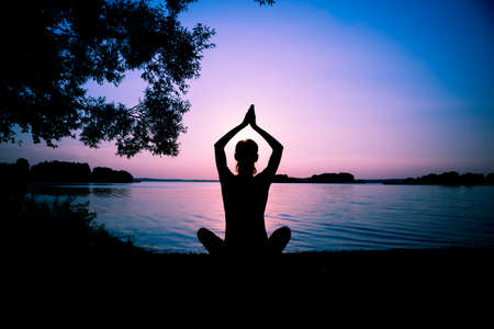 lake beach: Silhouette woman practicing yoga posing on beach at sunset Stock Photo