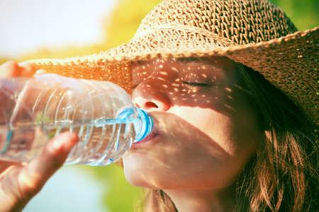 Mujer de agua potable en sol de verano Foto de archivo - 46616573