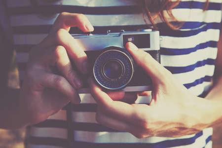 menina, segurando a câmera retro e tendo foto