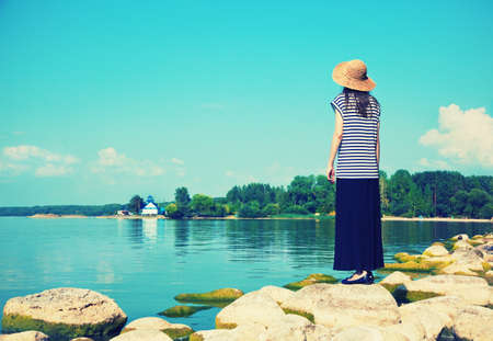 solitude: woman standing alone at sea coast and looking at water Stock Photo