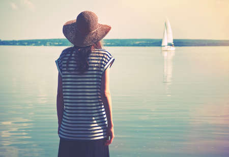 girl in a hat: woman standing alone at sea coast and looking at ship