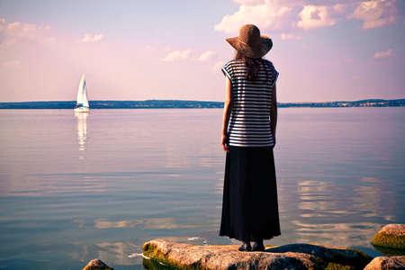 vrouw die zich alleen op zee kust en het kijken naar het schip Stockfoto