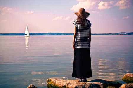 standing alone: woman standing alone at sea coast and looking at ship