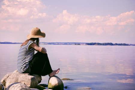 時尚女性獨自坐在石頭海岸,看著大海 版權商用圖片