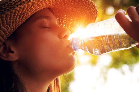 tomando agua: Mujer de agua potable en sol de verano