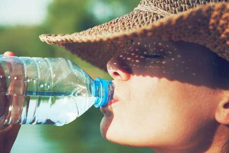 el agua: Mujer de agua potable en sol de verano