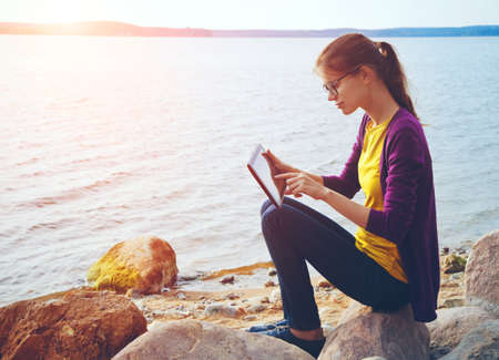 stone tablet: pretty girl using digital tablet at sunny sea stone coast