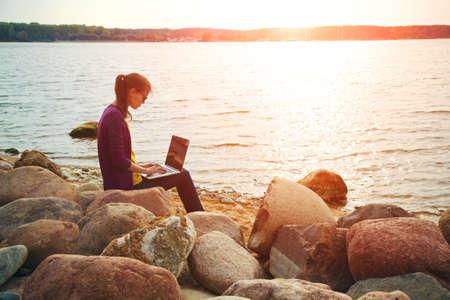 日当たりの良い海岸石でラップトップを使用してきれいな女の子 写真素材