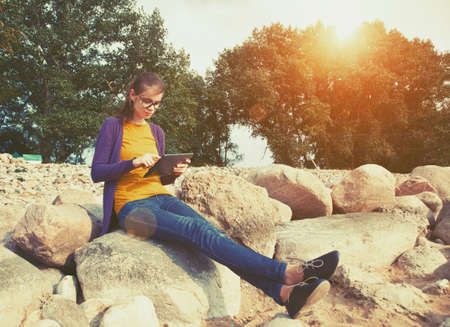 touch screen: pretty girl using digital tablet at stone coast