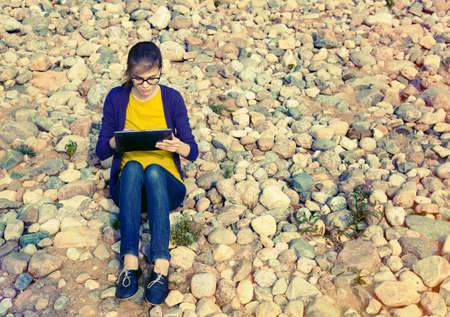 pretty girl using digital tablet at stone coast