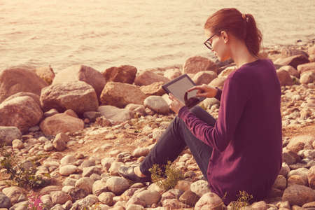 girl studying: pretty girl using digital tablet at sunny sea stone coast