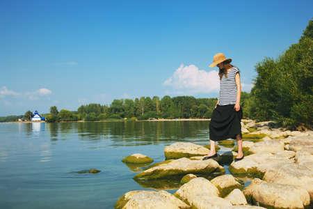 scandinavian landscape: stylish woman walking along stone sea coast