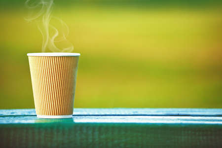 paper cup of coffee on natural outside background